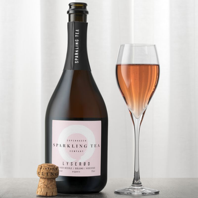Lyserod Copenhagen Sparkling Tea Pink in glass with open bottle
