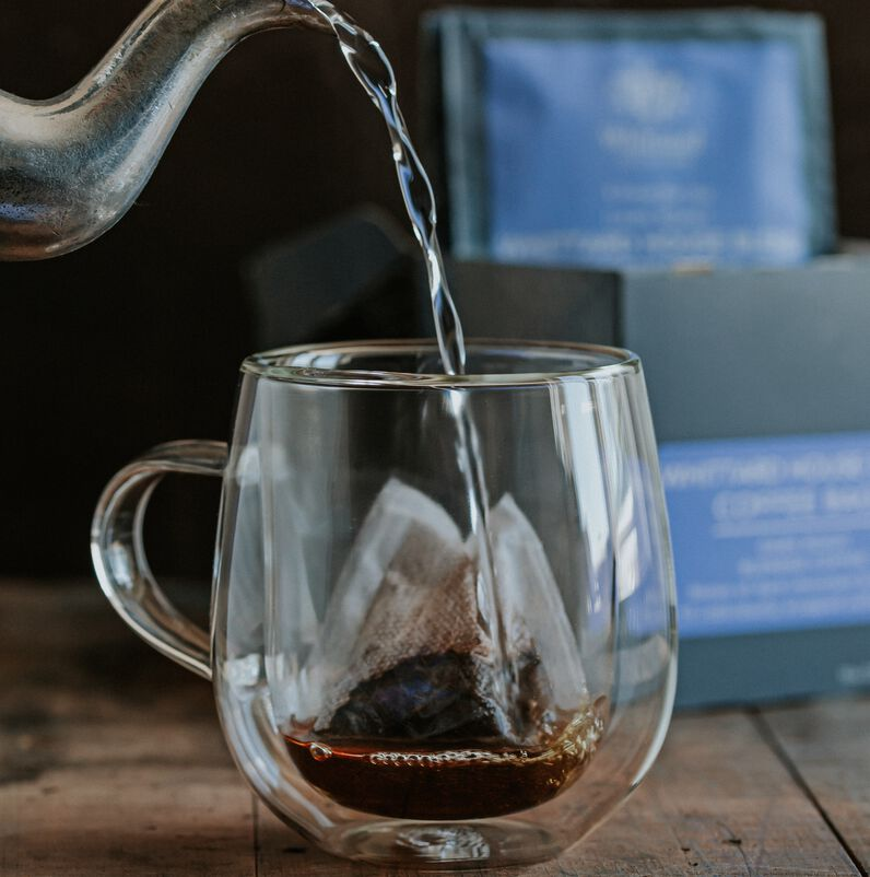 Coffee bag in a cup with boiling water pouring from kettle